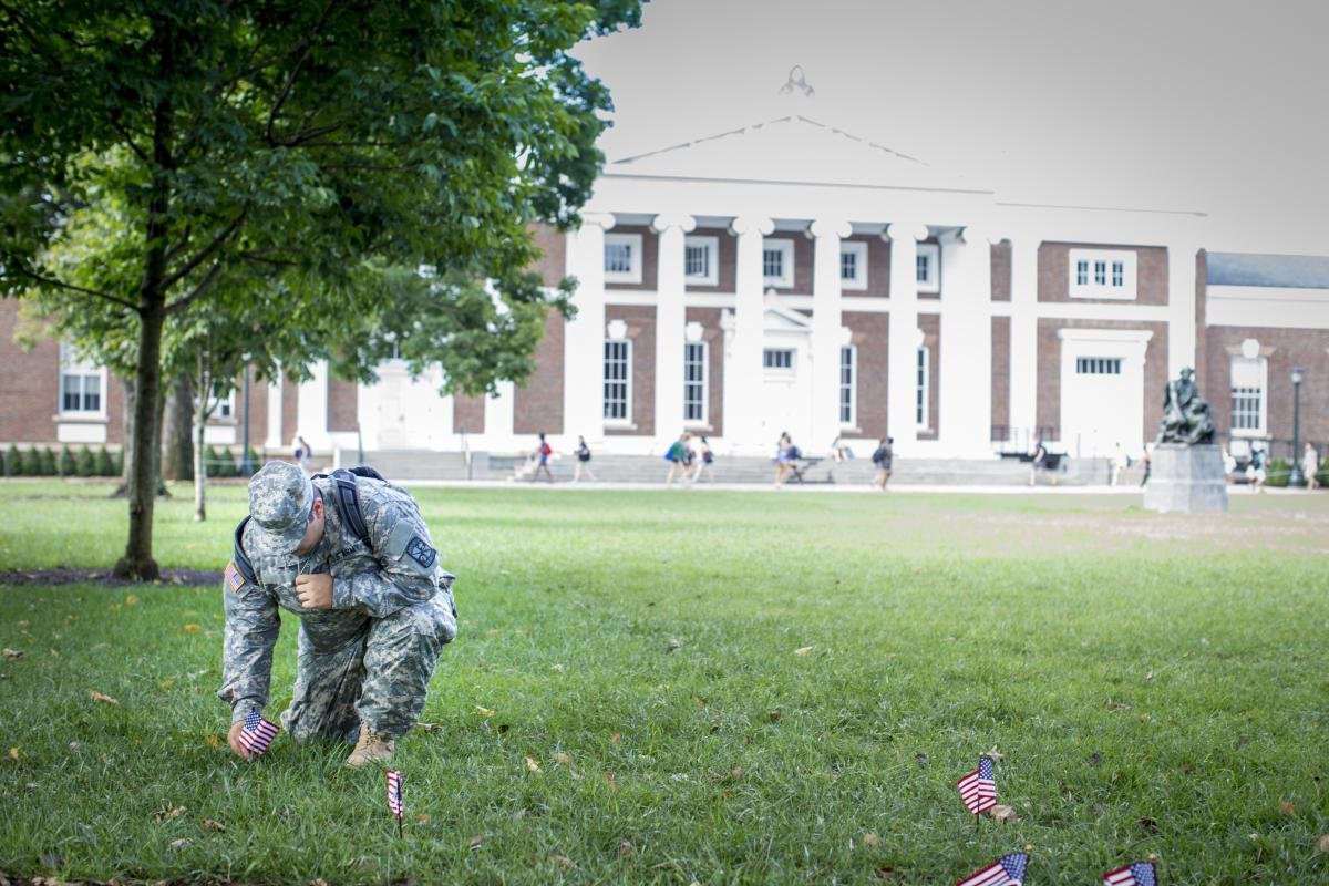 An image of a ROTC student placing flags on the UVA Lawn