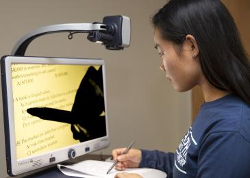 Student using assistive technology to review information on a computer screen.